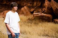 teen boy in Wyoming wilderness area, large red-brown boulders in background, copyspace Stock Photo - Royalty-Freenull, Code: 400-04059435