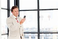 Senior businessman texting on his mobile phone with copy-space Stock Photo - Royalty-Freenull, Code: 400-04118257