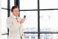 Senior businessman sending an sms on his mobile phone with copy-space Stock Photo - Royalty-Freenull, Code: 400-04118258