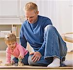 A young father is on the floor playing with his daughter.  He is smiling and looking at her.  Square framed shot. Stock Photo - Royalty-Free, Artist: avava, Code: 400-04124039