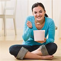eating ice cream - Attractive woman sitting on floor with crossed legs and eating ice cream. Square Stock Photo - Royalty-Freenull, Code: 400-04126364