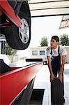 mechanic replacing car tyre in auto repair shop. Front view Stock Photo - Royalty-Free, Artist: diego_cervo, Code: 400-04126659