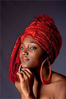 Beautiful African-American woman wearing a traditional tribal red orange head scarf and big orange hoop earrings, supporting her chin with hand, isolated. Stock Photo - Royalty-Freenull, Code: 400-04129583