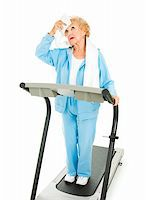 sweaty woman - Senior lady on a treadmill mops sweat from her forehead with a towel.  She doesn't like working out.  Isolated. Stock Photo - Royalty-Freenull, Code: 400-04132279