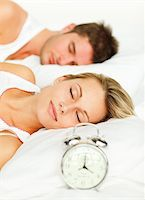 Attractive couple in bed with alarm clock going off Stock Photo - Royalty-Free, Artist: 4774344sean, Code: 400-04138169