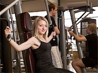 sweaty woman - Girl using an exercise machine at a health club with two men in the background Stock Photo - Royalty-Freenull, Code: 400-04147993