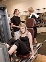 sweaty woman - Girl using an exercise machine at a health club with two men in the background Stock Photo - Royalty-Freenull, Code: 400-04148022