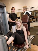 sweaty woman - Girl using an exercise machine at a health club with two men in the background Stock Photo - Royalty-Free, Artist: gemenacom, Code: 400-04148023