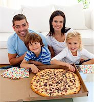 Happy family eating pizza on sofa all together Stock Photo - Royalty-Freenull, Code: 400-04152234