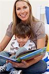 Smiling motherr reading a book with her son in bedroom Stock Photo - Royalty-Free, Artist: 4774344sean, Code: 400-04152310