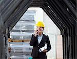 female engineer talking on mobile phone in construction site Stock Photo - Royalty-Free, Artist: diego_cervo, Code: 400-04154153