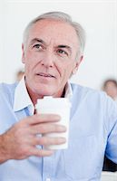 Senior businessman holding a drinking cup at work Stock Photo - Royalty-Freenull, Code: 400-04159692