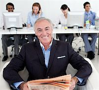 Senior manager reading a newspaper with his team in the background Stock Photo - Royalty-Freenull, Code: 400-04159700