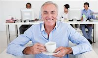 Senior businessman drinking a coffee with his team in the background Stock Photo - Royalty-Freenull, Code: 400-04159705