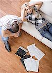 High angle view of a young couple frustrated while doing paperwork. Vertical shot. Stock Photo - Royalty-Free, Artist: cardmaverick, Code: 400-04162429