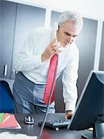 portrait of mature business man talking on the phone, looking at computer screen. Stock Photo - Royalty-Freenull, Code: 400-04163673