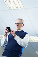 portrait of mature business man typing on mobile phone. Low angle view, Copy space Stock Photo - Royalty-Freenull, Code: 400-04163910