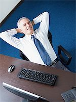 Mature business man leaning on chair with hands behind head, looking away and smiling. Copy space Stock Photo - Royalty-Freenull, Code: 400-04163922