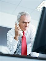 portrait of mature business man talking on the phone, looking at computer screen. Stock Photo - Royalty-Free, Artist: diego_cervo, Code: 400-04164037