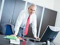 portrait of mature business man leaning on desk, looking at camera. Copy space Stock Photo - Royalty-Freenull, Code: 400-04164426
