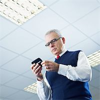 portrait of mature business man typing on mobile phone. Low angle view, Copy space Stock Photo - Royalty-Freenull, Code: 400-04164704