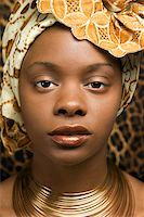 Close-up portrait of an African American woman wearing traditional African clothing in front of a patterned wall. Vertical format. Stock Photo - Royalty-Freenull, Code: 400-04164721