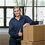 Young woman using hand truck to move boxes.  Vertically framed shot. Stock Photo - Royalty-Free, Artist: avava, Code: 400-04167538