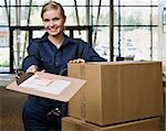 Young woman using hand truck to move boxes with delivery forms.  Horizontally framed shot. Stock Photo - Royalty-Free, Artist: avava, Code: 400-04167540