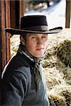 Attractive young man wearing a black cowboy hat. Bales of hay are in the background. Vertical shot. Stock Photo - Royalty-Free, Artist: iofoto, Code: 400-04169393