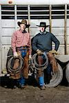 Two men wearing cowboy hats and leaning on the side of a livestock trailer. They are holding lariats. Vertical shot. Stock Photo - Royalty-Free, Artist: iofoto, Code: 400-04169417