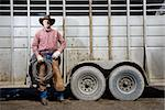 Man wearing a cowboy hat, leaning on the side of a livestock trailer. He is holding a lariat. Horizontal shot. Stock Photo - Royalty-Free, Artist: iofoto, Code: 400-04169418