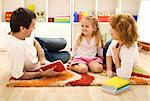 Story time - happy family with a child reading a book laying on the floor Stock Photo - Royalty-Free, Artist: ilona75, Code: 400-04173034
