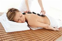 Delighted woman lying on a massage table having a stone therapy Stock Photo - Royalty-Freenull, Code: 400-04192067