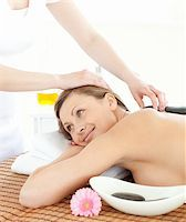 Portrait of a pensive woman having a massage with stones at the spa Stock Photo - Royalty-Freenull, Code: 400-04192112