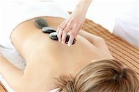 Radiant woman having a stone therapy against a white background Stock Photo - Royalty-Freenull, Code: 400-04192134