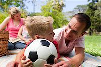 female playing soccer - Father and son holding a soccer ball with their family reading in the background at a picnic Stock Photo - Royalty-Freenull, Code: 400-04195742