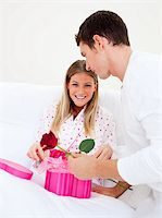 Attractive husband giving a present to his wife in the bedroom Stock Photo - Royalty-Freenull, Code: 400-04195869