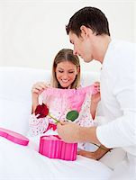 Charming husband giving a present to his wife in the bedroom Stock Photo - Royalty-Freenull, Code: 400-04195870