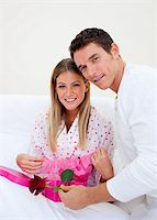 Elegant husband giving a present to his wife in the bedroom Stock Photo - Royalty-Freenull, Code: 400-04195871