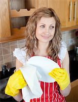 rubber apron woman - Smiling caucasian woman drying dishes in the kitchen Stock Photo - Royalty-Freenull, Code: 400-04202343