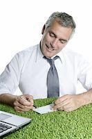 senior businessman signing bank check over green grass desk sport ecology Stock Photo - Royalty-Freenull, Code: 400-04204945