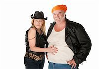 Woman in leopard skin cowgirl outfit flirting with big bellied man Stock Photo - Royalty-Freenull, Code: 400-04205705