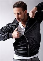 skinny man muscle pose - Smart male model giving movement with black jacket on a isolated grey background Stock Photo - Royalty-Freenull, Code: 400-04209220