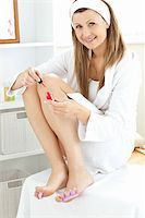 Beautiful young woman varnishing her toenails in the bathroom at home Stock Photo - Royalty-Freenull, Code: 400-04217648