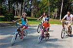 A modern family of two parents and two children, a boy and a girl, cycling together. Stock Photo - Royalty-Free, Artist: darrenbaker, Code: 400-04219475