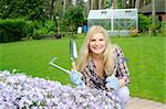 Pretty woman with gardening tools outdoors near flower hill. greenhouse on the background Stock Photo - Royalty-Free, Artist: smartfoto, Code: 400-04235651