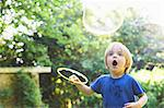 Boy making oversized bubble in backyard Stock Photo - Premium Royalty-Free, Artist: ableimages, Code: 649-04247854