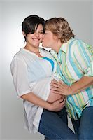 pregnant women kissing - Mother  touching pregnant daughter's belly Stock Photo - Premium Royalty-Freenull, Code: 618-04251701