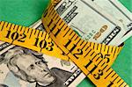 Money squeezed by a measuring tape representing a tight holiday budget. Stock Photo - Royalty-Free, Artist: brookebecker                  , Code: 400-04263611