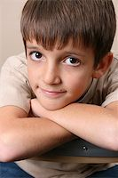 Young boy with big eyes, resting on a chair back Stock Photo - Royalty-Freenull, Code: 400-04264481